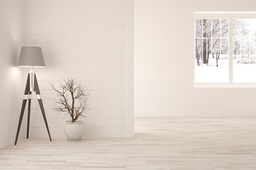 White room with lamp and winter landscape in window. Scandinavian interior design