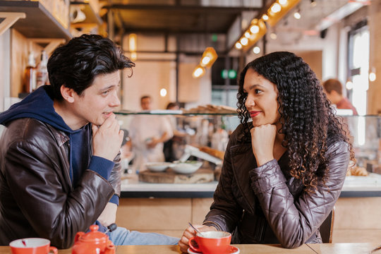 Young Multi-ethnic Couple Talking in a Pub.