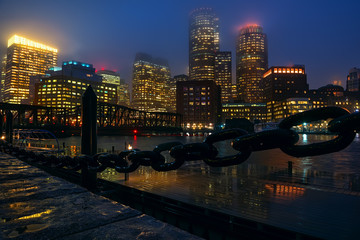 Fotobehang - View of Boston skyscrapers night. Rainy foggy weather, brilliant paving and lights of skyscrapers.