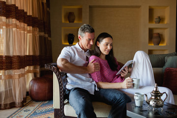 Couple using digital tablet at living room.