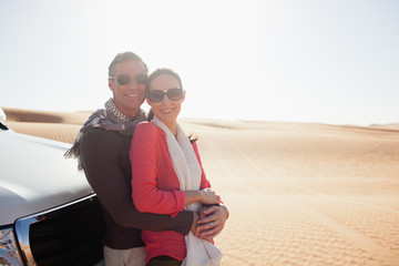 Portrait of couple embracing at desert.