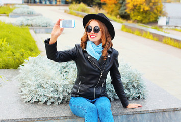 Fashion cool young smiling girl taking self portrait on smartphone in city park