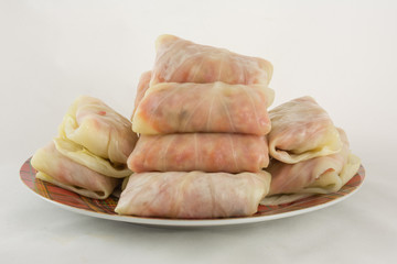 Cabbage rolls on a plate on white background