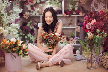 Beautiful asian woman florist in pink dress with bouquet of flowers in hands in flower store