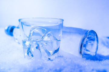 Bottle of vodka in the snow with glass filled with ice cubes