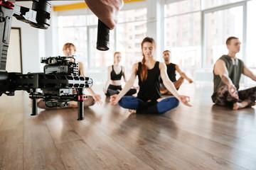 Video shooting of people doing yoga and meditating. Backstage