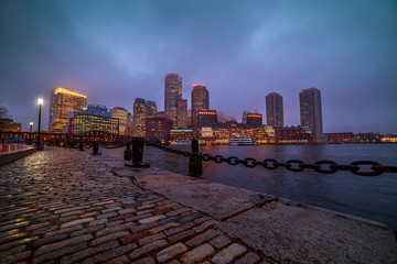 Wall Mural - View of Boston skyscrapers night and promenade.   The tops of the buildings in the fog and haze. Rainy foggy weather, brilliant paving and lights of skyscrapers.