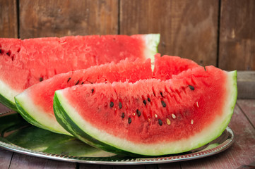 Slices of watermelon on a metal dish on a wooden background. Rustic style.