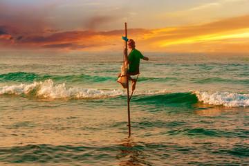 Fisherman in ocean . Traditional sri lankan sit fisherman.