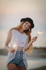 Teenage beautiful girl with sparklers on the beach at sunset
