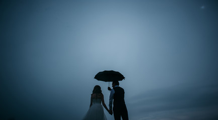 the bride and groom under an umbrella on a background of dark sky