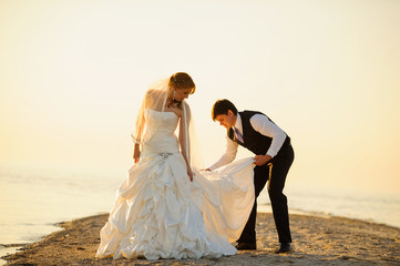 bride and groom walking on the sand on the shore