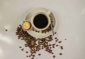 top view of black coffee in a white cup with cream muffin, spilled coffee beans
