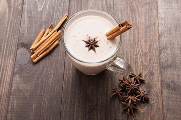 Masala chai with spices cinnamon, cardamom, ginger, clove and star anise on wooden background