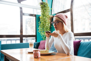 Woman taking pictures of food with mobile phone in cafe