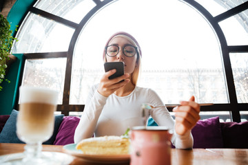 Woman taking photos of her dessert with smartphone in cafe
