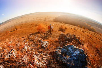 Wide angle view of cyclist standing with mountain bike on trail at sunset