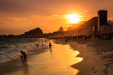 Fotomurales - Sunset View in Copacabana Beach with Mountains in Horizon and Tall Hotel Building, Rio de Janeiro