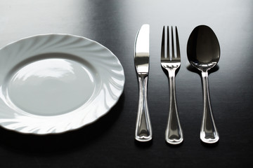 Cutlery on a black background. Fork, spoon, knife, plate.