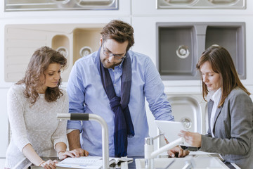 Customers consulting saleswoman in shop for kitchen sinks