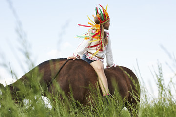 Girl wearing feather headdress riding horse in meadow