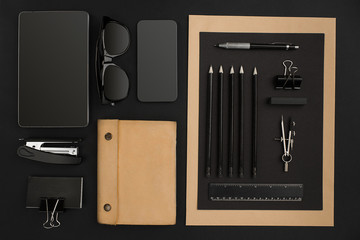 Office desktop with various black objects on  background