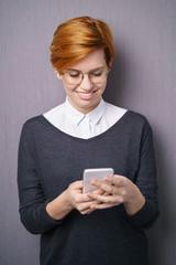 lächelnde frau liest eine nachricht auf ihrem mobiltelefon