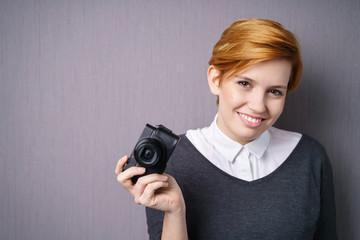 lächelnde junge frau mit einer digitalkamera