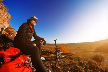 Mountain biker looking at view on bike trail in spring landscape. Male rider resting on cycling trip in nature.