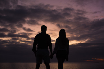 Silhouette of a young couple at sunset on the beach near the ocean