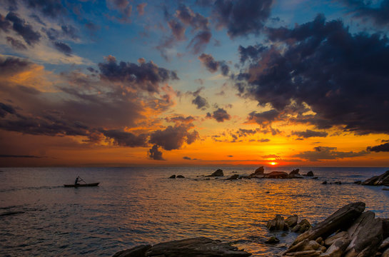 Beautiful sunrise over lake Malawi with rock formation and a canoe gliding trough the water under colorful cloudy sky. The bright orange sunlight on the horizon gradually changes color to blue