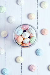 Color zephyrs in glass jar on white wooden table