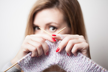 Beautiful smiling woman holding knitting in hands. Blurred background