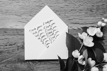"Black and white art photography monochrome, the inscription ""I love you"" writing on the envelope calligraphy. Flowers and jasmine petals on wooden background. Wedding invitation card. Valentine day.;"