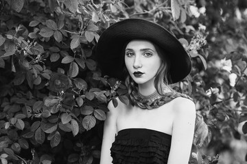 Black and white art photography monochrome, girl with and pale skin in hat and dress with belt. Woman with long plait against the backdrop of bush roses