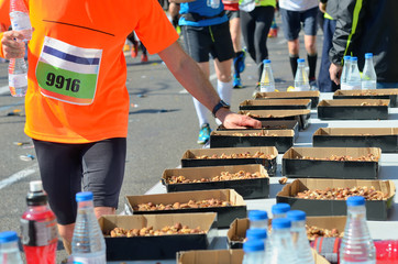 Marathon running road race, runners hand taking food and drinks on refreshment point, sport, fitness and healthy lifestyle concept