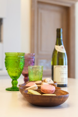 Dessert, wine and glasses of colored glass on a table made of wood