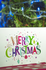 Christmas gifts and the words Merry Christmas on the background of the Christmas tree and lights