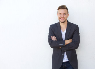 attractive young businessman smiling against white wall