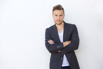 confident young business man standing against white wall