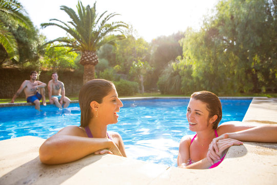 Friends in swimming pool chatting