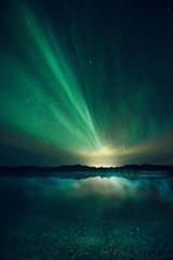 Aurora borealis over water at night, Thingvellir, Iceland