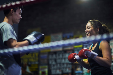 Male and  female boxers having boxing match in ring