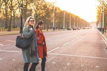 Two female friends crossing road, smiling