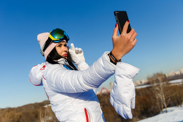 Beautiful brunette snowboarder photographing herselves