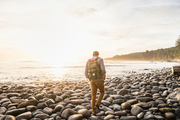 Rear view of man walking on beach in Juan de Fuca Provincial Park, Vancouver Island, British Columbia, Canada