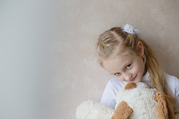 Smiling little girl holding a toy dog