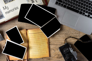 Old family photos on wooden background. Vintage pictures, camera, notepad and modern notebook. Flat lay. Blank photo frames