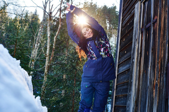 Woman in winter clothes practicing half moon yoga pose in snow by log cabin, Austria