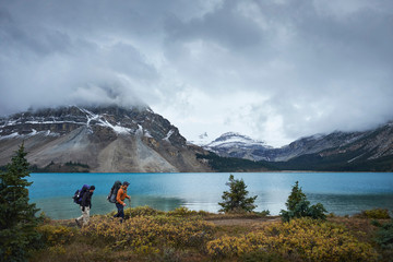 Hikers hiking by lake and snow capped mountains, Banff, Alberta, Canada